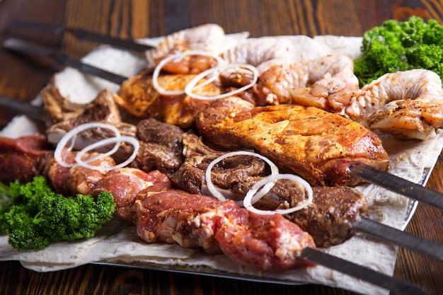 Ассорти из мяса на шпажках. сырая свинина, телятина и курица готовы приготовить. sashlik