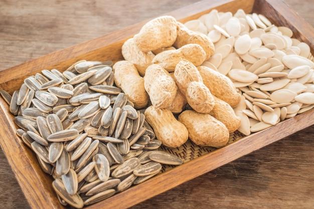 Ассорти из цельного зерна подсолнечника, арахиса и тыквы на деревянном столе