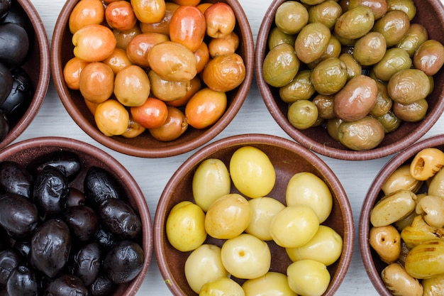 Assorted olives in a clay bowls on white wood plank. close-up.