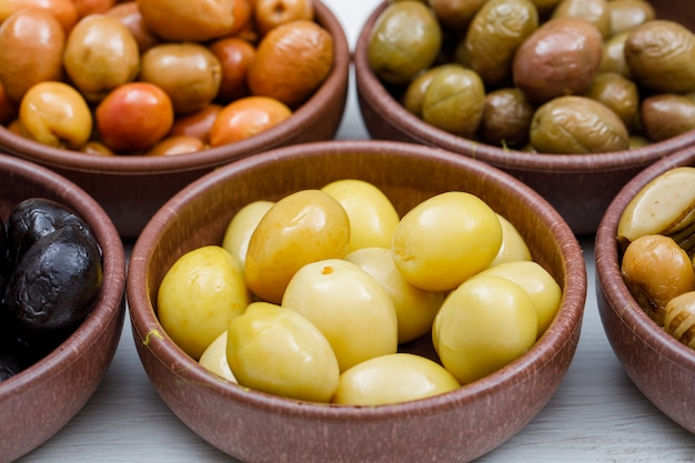 Assorted olives in a clay bowls on white wood plank, side view.