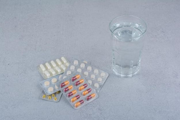 Confezioni assortite di capsule e pillole con bicchiere d'acqua.
