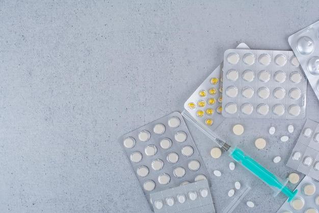 Confezioni assortite di farmaci e siringa vuota sulla superficie in marmo