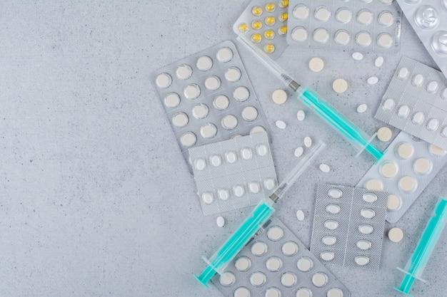Ассорти из упаковок лекарств и пустых шприцев на мраморной поверхности.