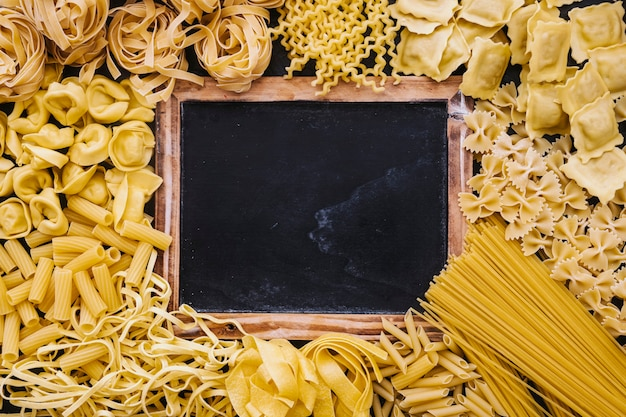 Assorted pasta around blackboard