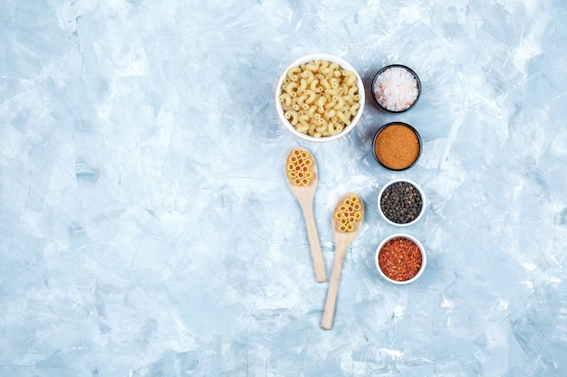 Assorted pasta in bowl and wooden spoons with spices top view on a grungy grey background