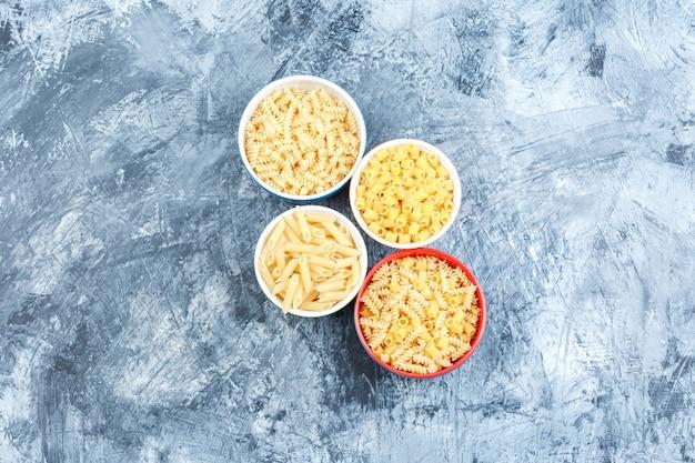 Pasta assortita in ciotole su uno sfondo di gesso grigio. vista dall'alto.