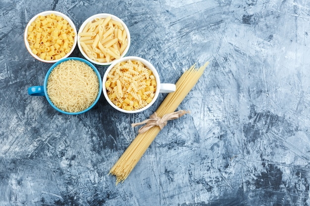 Assorted pasta in bowls on a grey plaster background. top view.