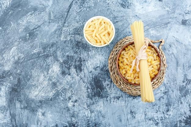 Pasta assortita in ciotole su intonaco grigio e sfondo tovaglietta di vimini. vista dall'alto.
