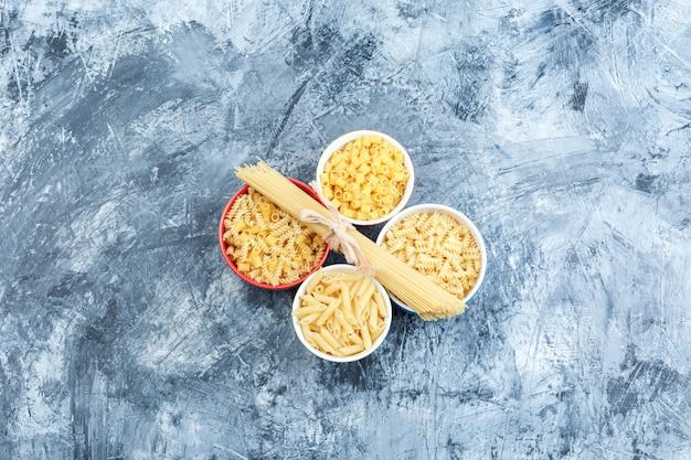 Pasta assortita in ciotole su una priorità bassa grungy dell'intonaco. laici piatta.