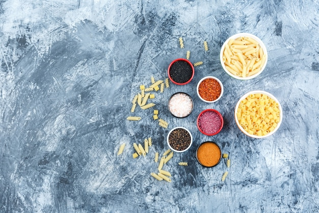Assorted pasta in bowls with spices top view on a grey plaster background