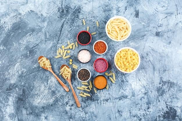 Pasta assortita in ciotole e cucchiai di legno con vista dall'alto di spezie su uno sfondo di gesso grigio