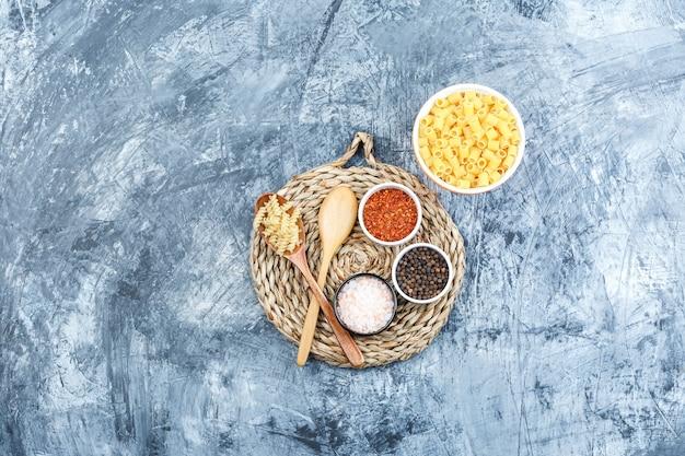 ボウルと木のスプーンの各種パスタ、灰色の石膏と枝編み細工品のプレースマットの背景にスパイスの上面図