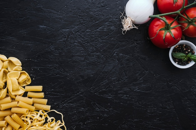 Assorted pasta near vegetables and spices