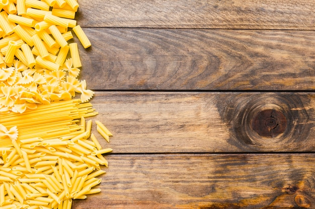 Assorted pasta on wooden tabletop Free Photo