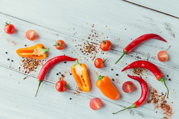 Assorted peppers, cherry tomatoes and spices on light wooden table