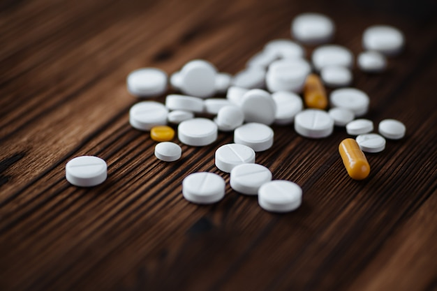 Assorted pharmaceutical medicine capsules and tablets on wooden background.