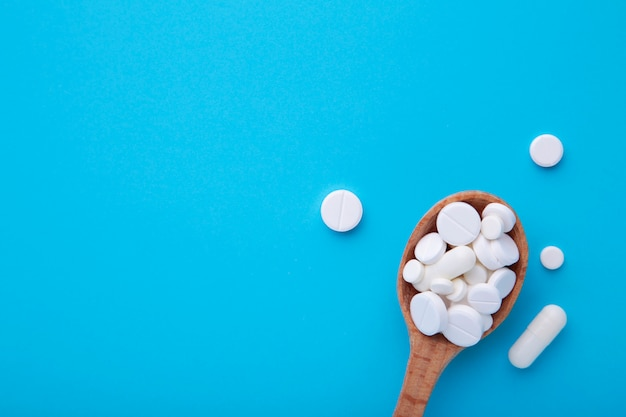 Assorted pharmaceutical medicine pills, tablets and capsules on wooden spoon on blue background