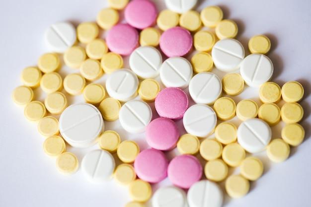 Ассорти из таблеток фармацевтической медицины. желтые и розовые таблетки на белом фоне.