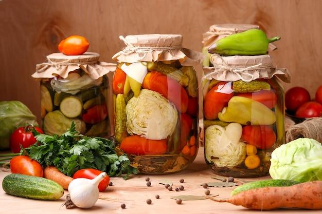 瓶に入った野菜の盛り合わせ:きゅうり、トマト、キャベツ、ズッキーニ、ピーマンとニンニク、ディル、月桂樹の葉を木の表面に瓶に入れて、水平方向の写真、素朴なスタイル
