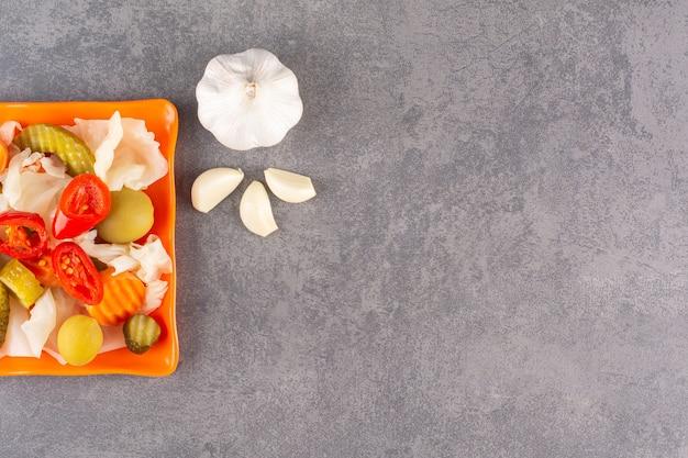 石のテーブルの上に置かれたボウルに野菜の盛り合わせ。