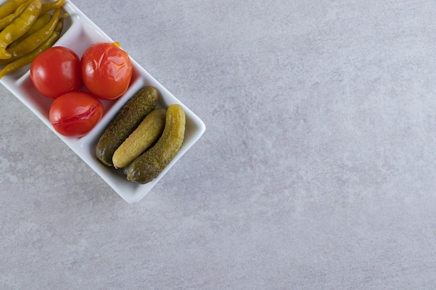 Assorted pickles vegetables placed on a stone background.