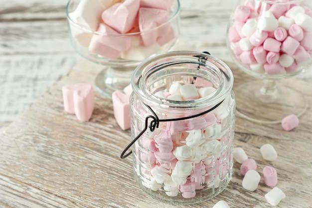 木製の背景にガラスのカップにピンクと白のマシュマロの盛り合わせ。ホットチョコレートやカカオ用のハート型マシュマロ。