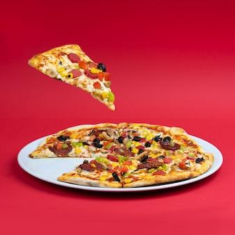 빨간 배경을 공중에 띄우는 모듬 피자와 피자 조각