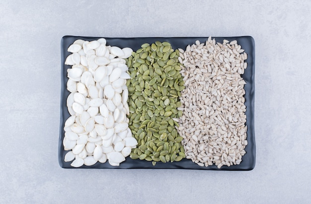 Assorted plate of pepitas, sunflower seeds and white pumpkin seeds on marble surface