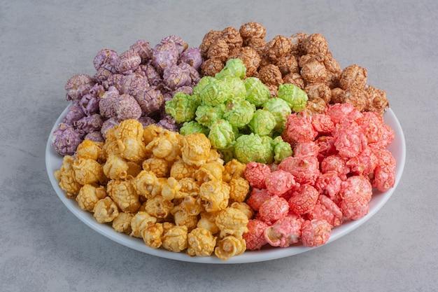 Caramelle assortite di popcorn servite in piccole ciotole di vetro su marmo.