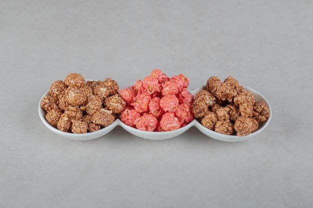 Caramelle assortite per popcorn su un piatto da portata tripla sul tavolo di marmo.