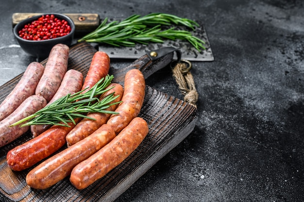 Assorted raw chorizo sausages on a wooden cutting board.