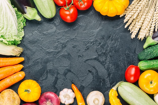 黒い石の背景に有機生野菜の盛り合わせ。ライ麦、キュウリ、トマト、ナス、メロン、カボチャ、ニンニクと農家のテーブルの秋の季節限定フレーム