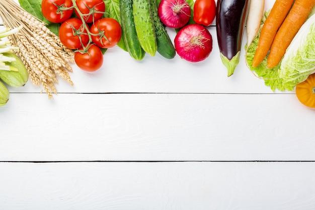 白い木製のテーブルに生の有機新鮮野菜の盛り合わせ。新鮮な庭のベジタリアン料理。きのこ、ライ麦、きゅうり、トマト、ナス、キャベツ、ニンジンと農家のテーブルの秋の季節のイメージ。
