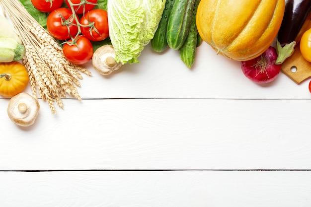 흰색 나무 테이블에 모듬된 원시 유기농 신선한 야채. 신선한 정원 채식 음식. 버섯, 호밀, 오이, 토마토, 가지, 호박 등이 있는 농부 테이블의 가을 계절 이미지.