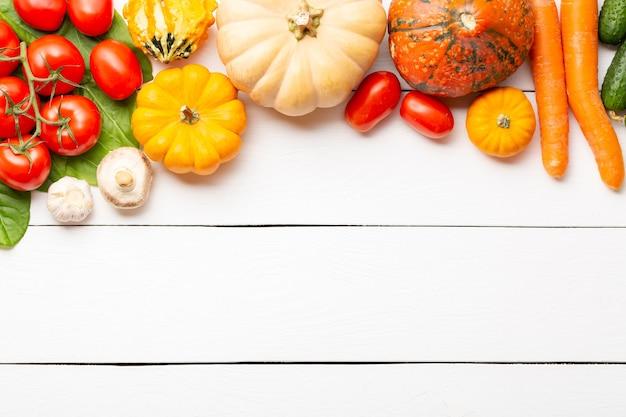 白い木製のテーブルに生の有機新鮮野菜の盛り合わせ。新鮮な庭のベジタリアン料理。きのこ、ライ麦、きゅうり、トマト、ナス、カボチャと農家のテーブルの秋の季節のイメージ。