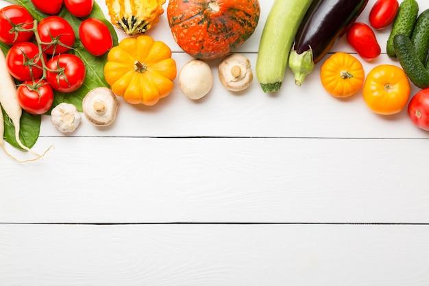 Ассорти из сырых органических свежих овощей на белом деревянном столе.