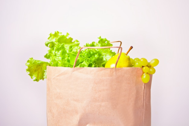 Assorted raw organic green vegetables and friuts in the paper bag.