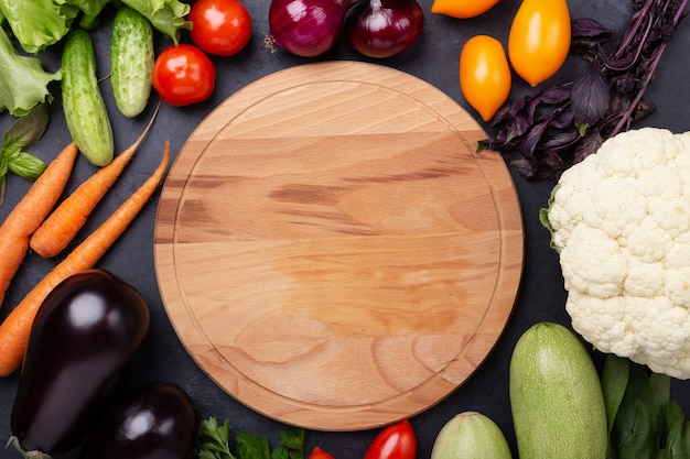 Assorted raw organic vegetables and cutting board on dark stone background
