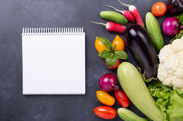 Assorted raw organic vegetables and notebook on dark stone background