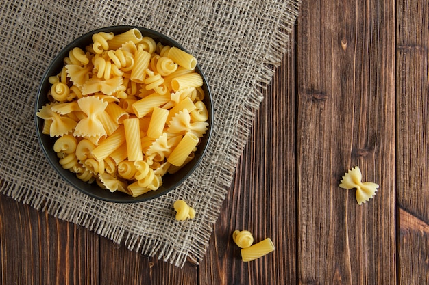 Assorted raw pasta in a bowl on wooden and piece of sack background. flat lay.