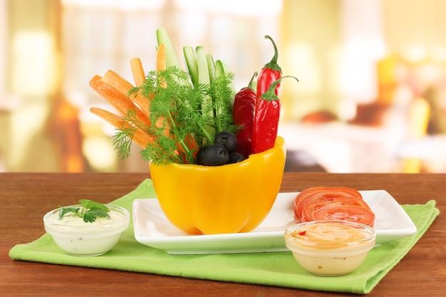 さまざまな生野菜が明るい背景の木製テーブルのペッパーボウルにスティック