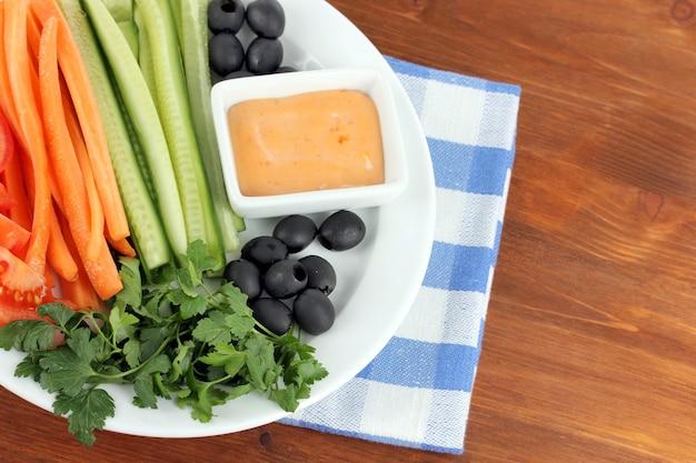 Ассорти из сырых овощных палочек в тарелке на деревянном столе