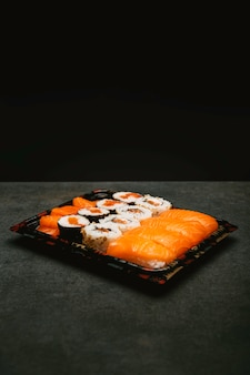 Assorted rice sushi inside three tupper black reusable tray on gray background
