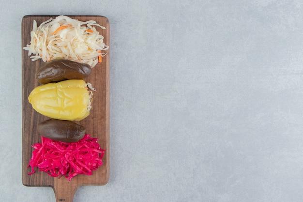 Sottaceti salati assortiti su tavola di legno.