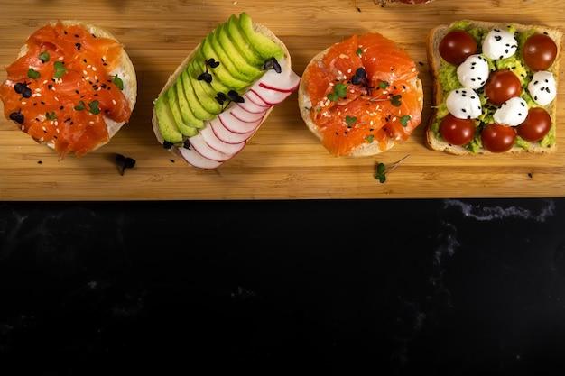 ボード上に横たわっている魚、チーズ、肉、野菜の盛り合わせサンドイッチ