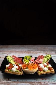 검정 잉크 판 및 나무 배경에 생선, 치즈, 고기, 야채와 모듬 된 샌드위치.