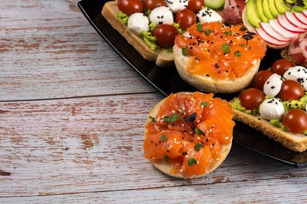 검정 접시에 생선, 치즈, 고기 및 야채와 함께 모듬 샌드위치