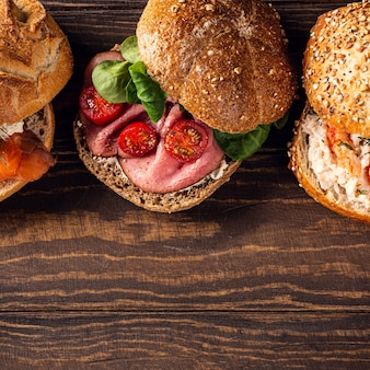 Assorted sandwiches on wooden surface. healthy food concept with copy space. top view