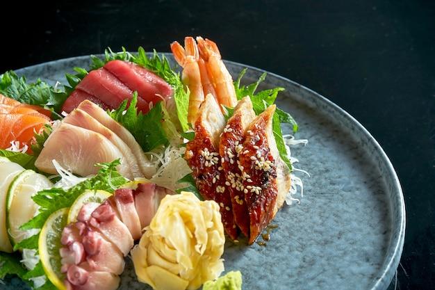 鮭、エビ、マグロ、タコ、ホタテ、ウナギの刺身盛り合わせ。クラシックな日本料理。食品デリバリー。黒で隔離