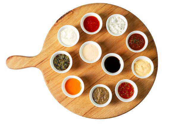Assorted sauces in bowls on a wooden board